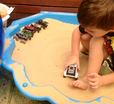 Boy, playing, sand, sandpit, toy monster truck, race, racing, track